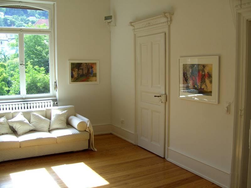 Blick in die Galerieräume, es hängen Gemälde an der Wand und eine Couch steht vor einem Fenster.